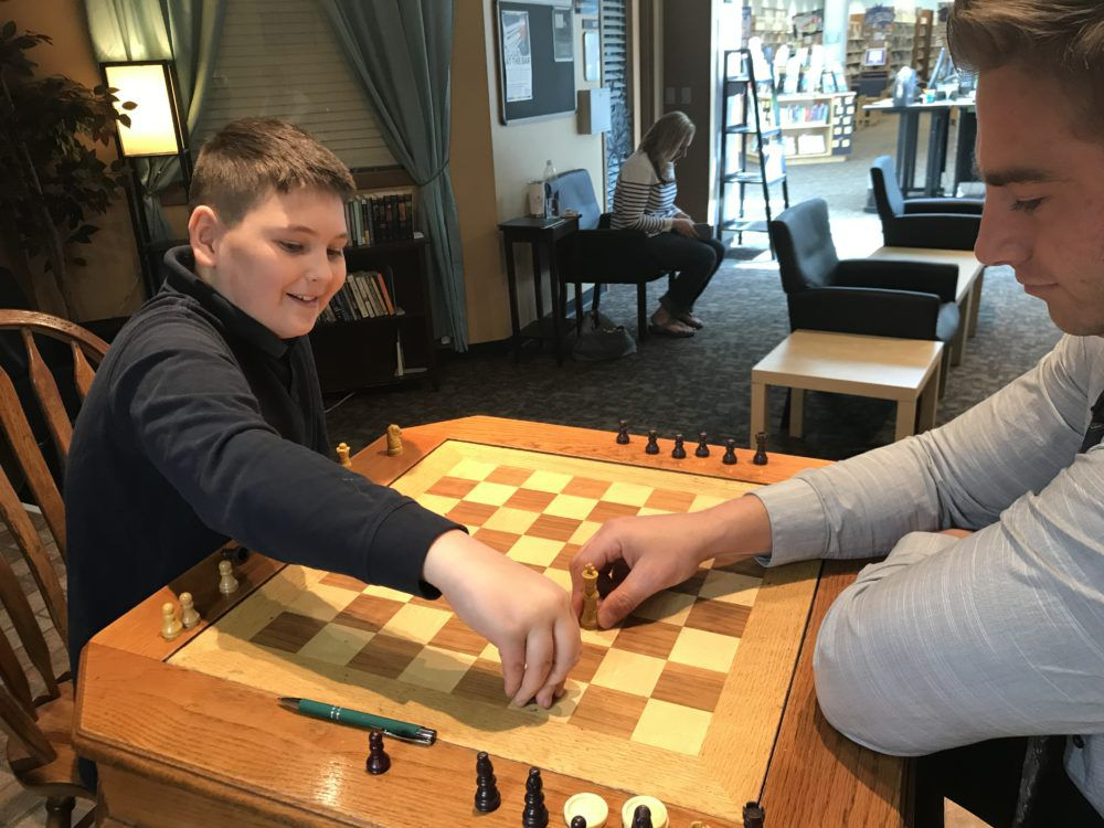 Jake DiProfio plays chess at the library with his teacher, Zak Johnson.