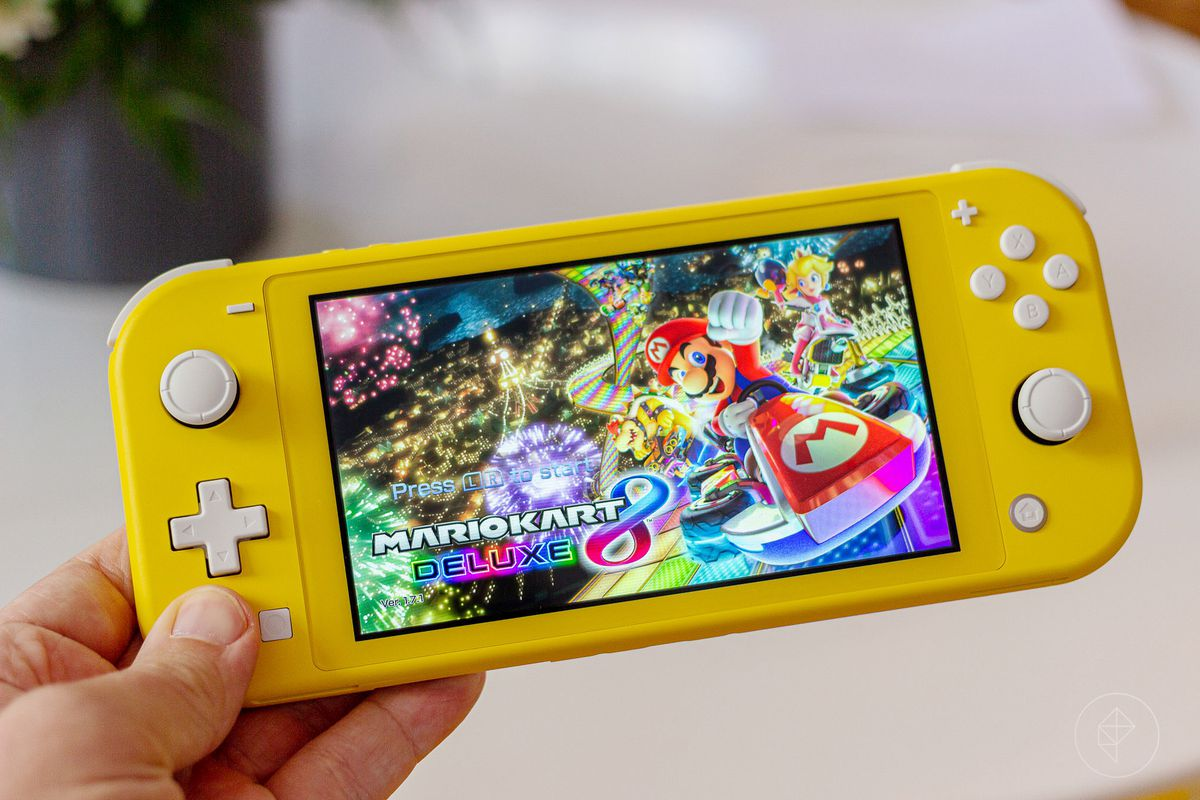 a hand holding a yellow Nintendo Switch Lite showing Mario Kart 8's title screen