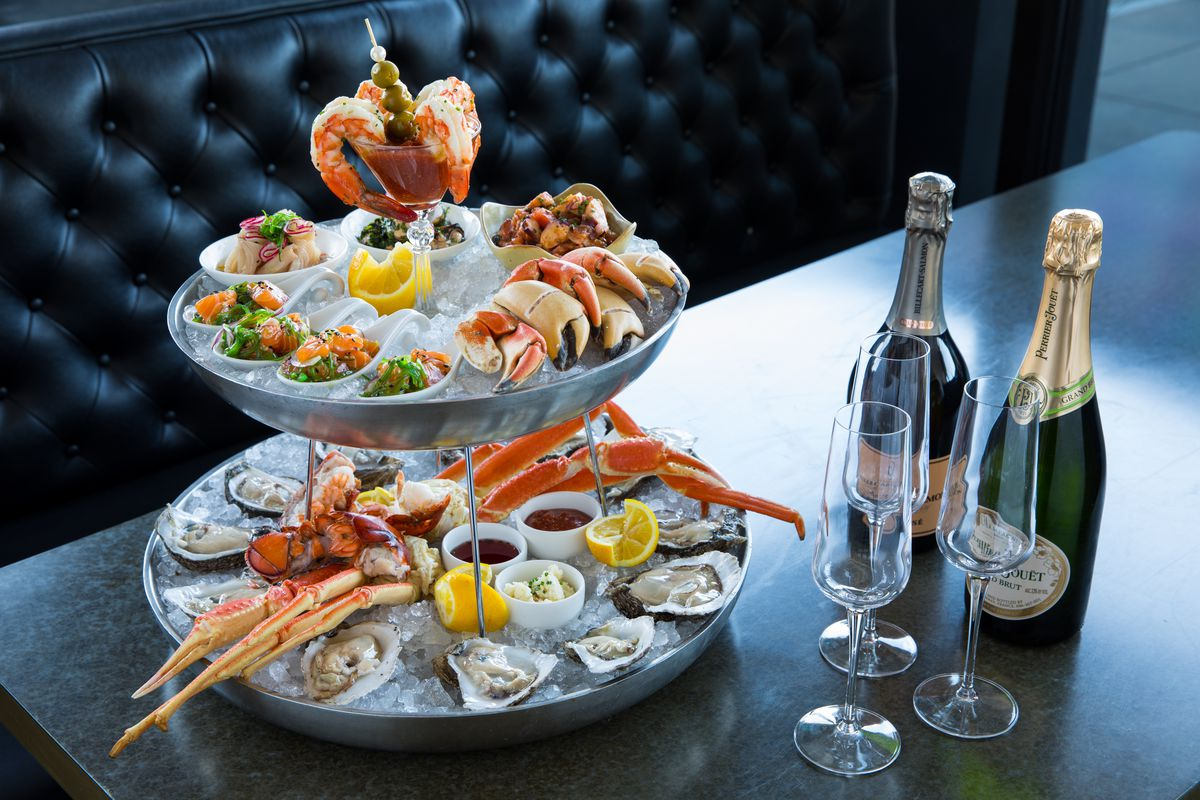 Seafood tower with shrimp, oysters, stone claw crabs, king crab legs, and sauces