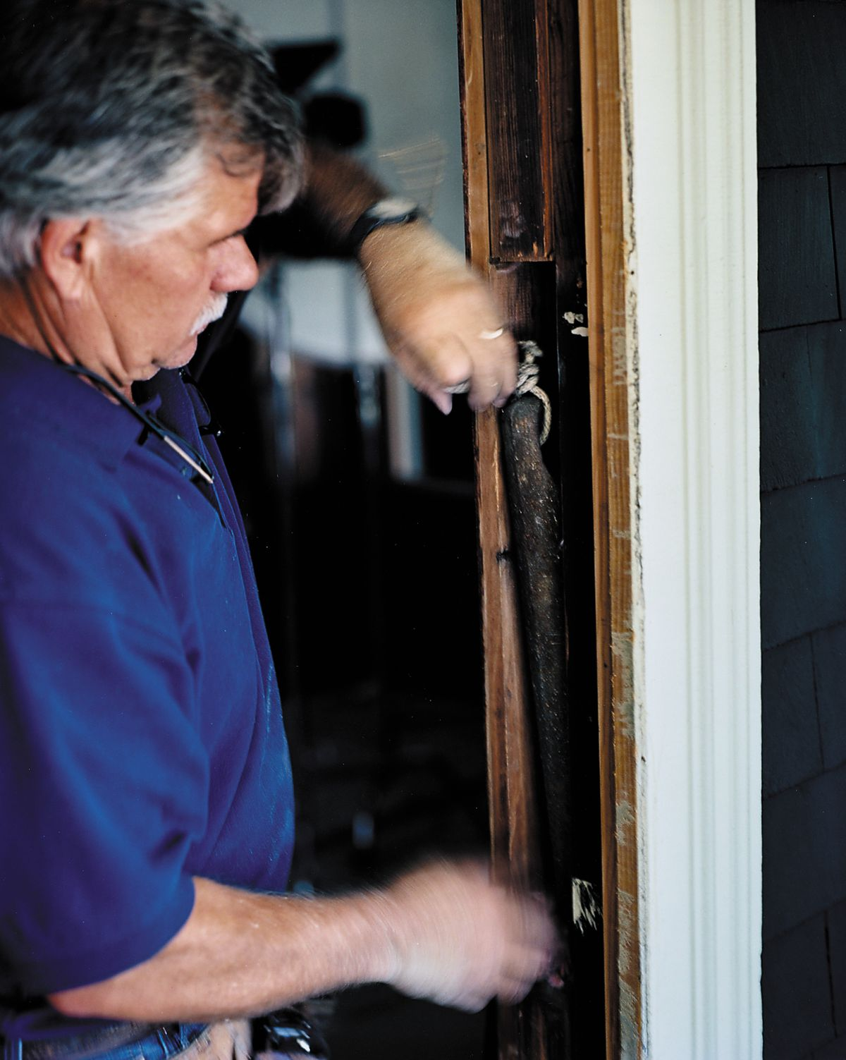 Man Removes Old Sash Weights Off Window