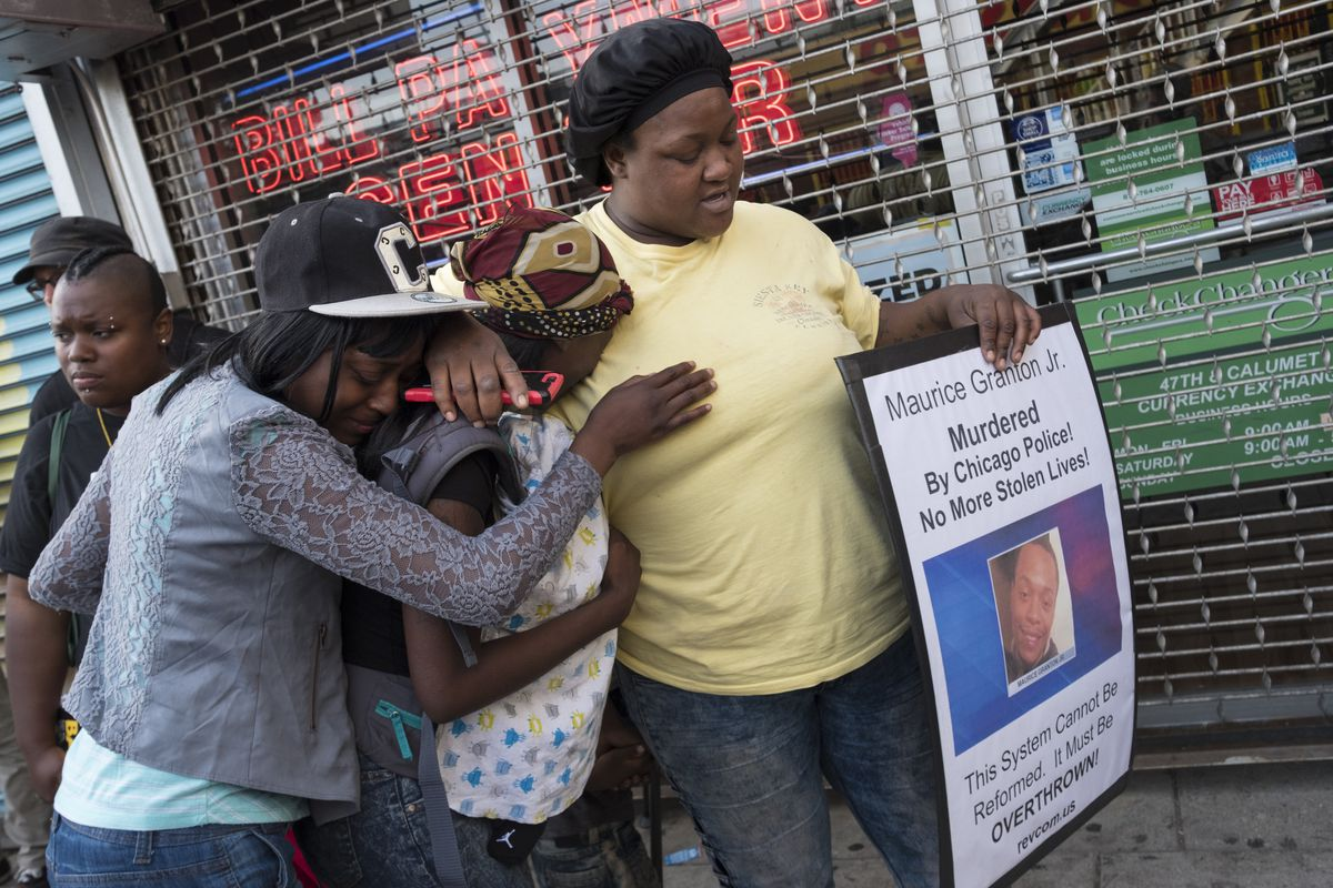 At a Thursday night vigil on 47th and Prairie, Shaumanika Jones (right) comforts Teresa Richardson (center), who is Maurice Granton Jr.'s sister. Granton was fatally shot by a Chicago Police officer Wednesday night during a Bronzeville foot chase.   Rick