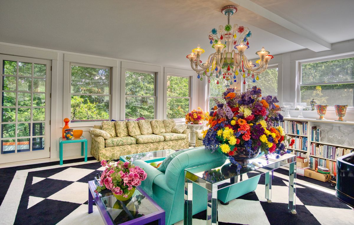 A living room has black and white flooring, a turquoise couch, large flowers, a colorful chandelier, and big windows.