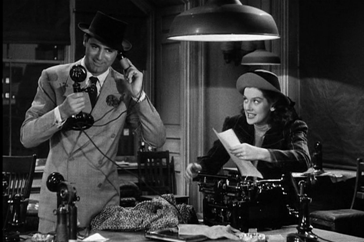 """Cary Grant and Rosalind Russell play reporters in the movie """"His Girl Friday"""": He holds an old-fashioned phone while she types on a typewriter."""