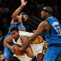 Los Angeles Lakers center Andrew Bynum, middle, battles to keep the ball from Dallas Mavericks center Brendan Haywood, right, and Mavericks guard Vince Carter during the first half of an NBA basketball game, Sunday, April 15, 2012, in Los Angeles.