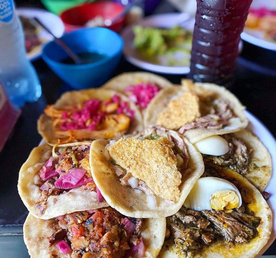 A tray stacked with several types of tacos, including ingredients like chicharron, boiled egg, meat, and pickled vegetables