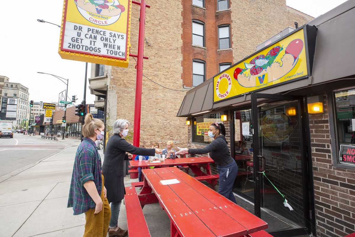 Two humans who have no idea what to expect waiting at the Wiener's Circle.