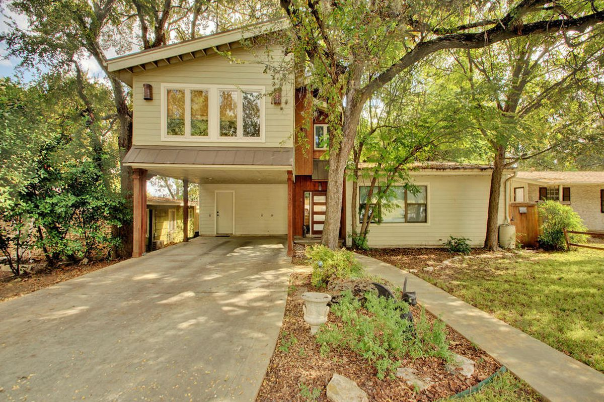 midcentury modern with flat roof, white birk with large two-story addition with carport underneath