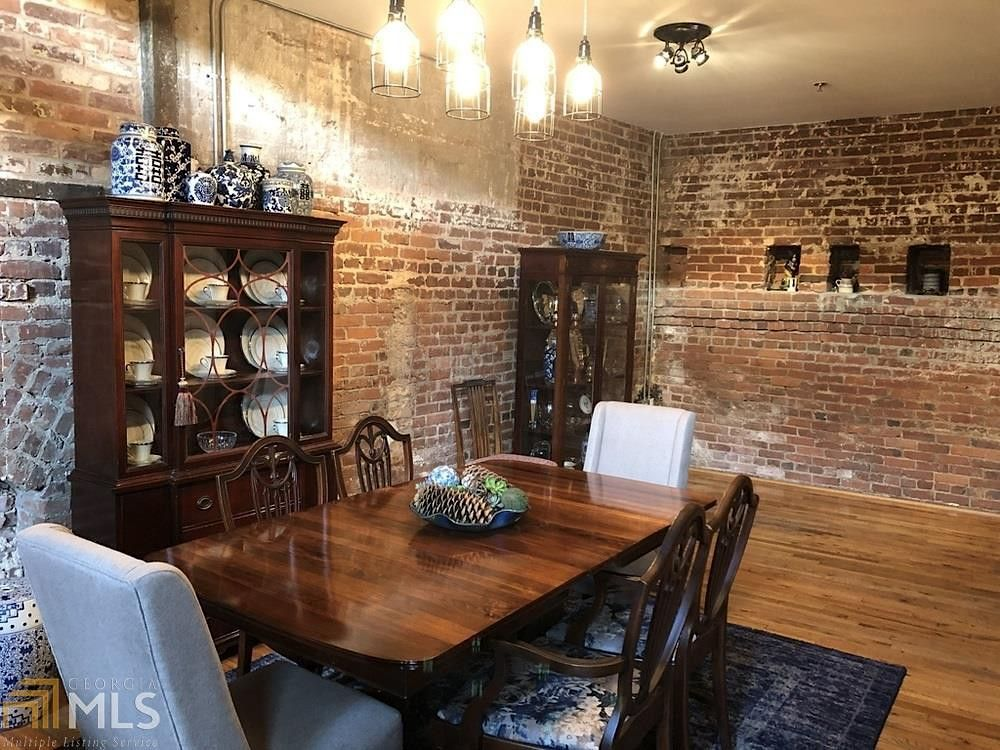 A dining room with brick wall all around it and pendent lights.