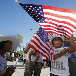 Osiris, left, and Yatziri Gaytan wave flags during a prayer vigil in Salt Lake City, Thursday, June 27, 2013.