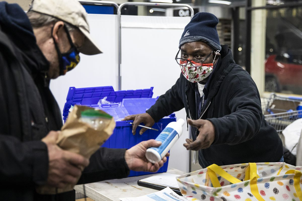 """Keith Belton, right, a peer advocate at the Night Ministry, hands """"harm reduction"""" products, such as hand sanitizer, to a homeless person at the CTA's Blue Line Forest Park station in February."""