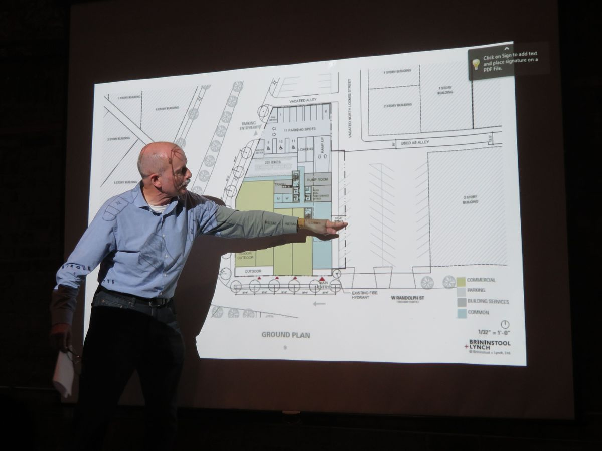 A man in a dark room stands in from of a projected overhead image showing a building's lobby, retail space, parking, and surrounding streets and sidewalks.