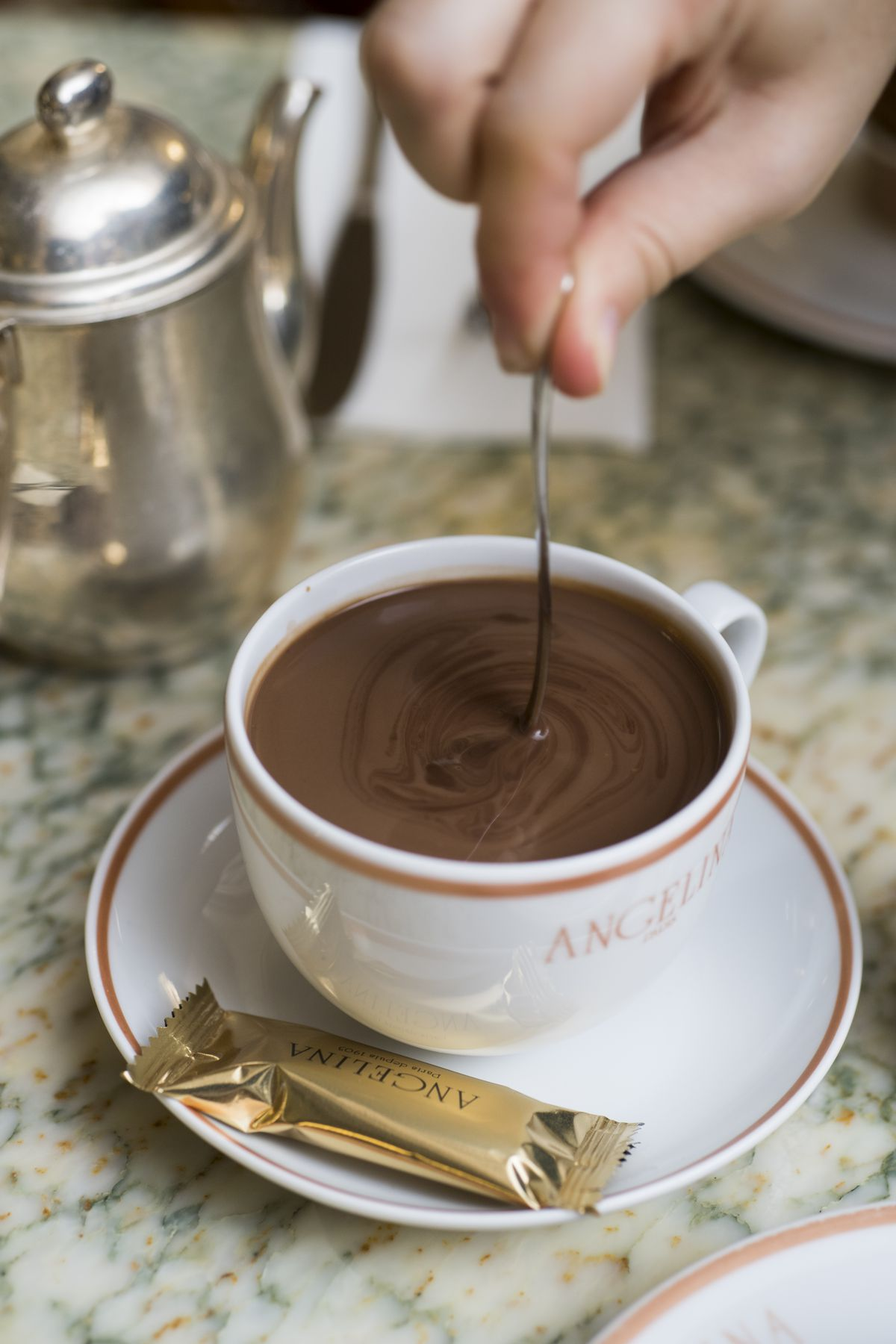 A silver spoon is being dipped into a white cup that holds thick hot chocolate