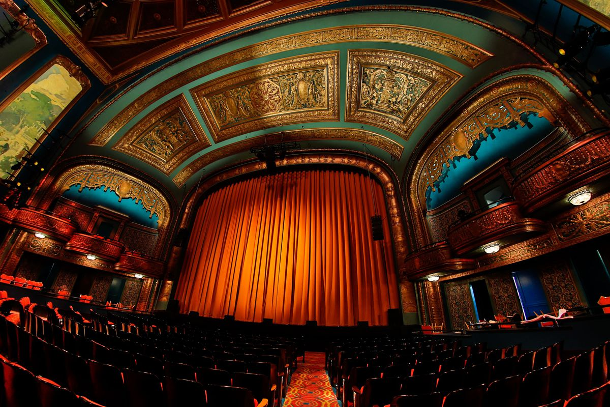 The interior of the Curran Theatre, with the red stage curtain down and the camera tilted up to emphasize the gold leaf on the ceiling.