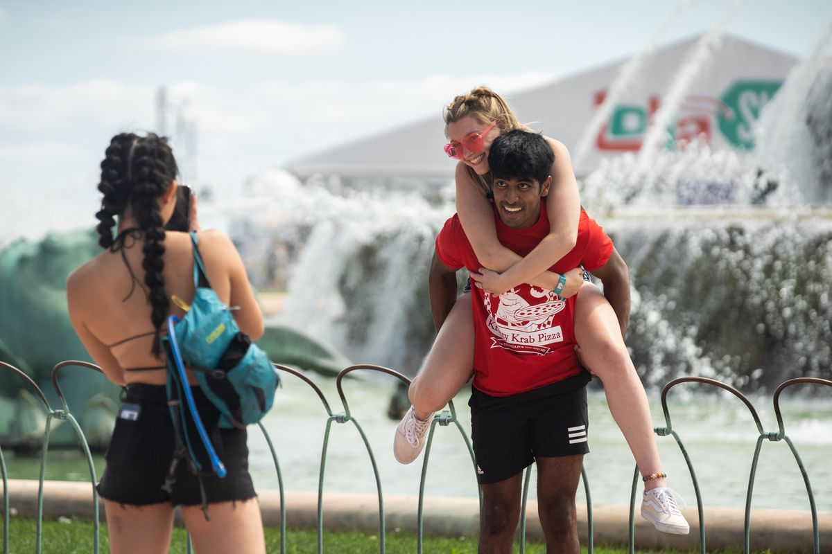 Hailey Thill, Monica Fronczek and Nick Dorai take pictures near Buckingham Fountain.