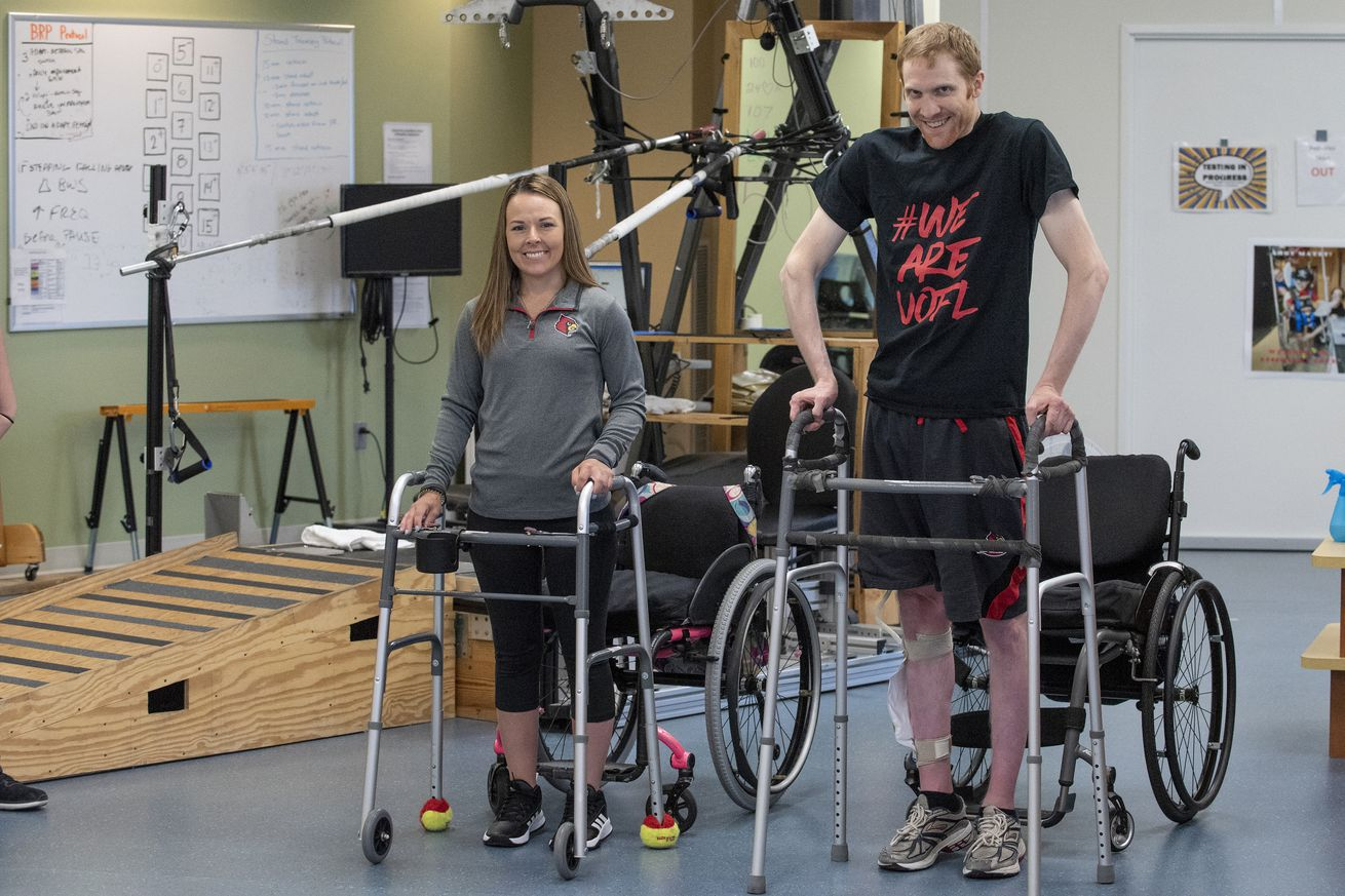 two people with paralysis walk again using an implanted device