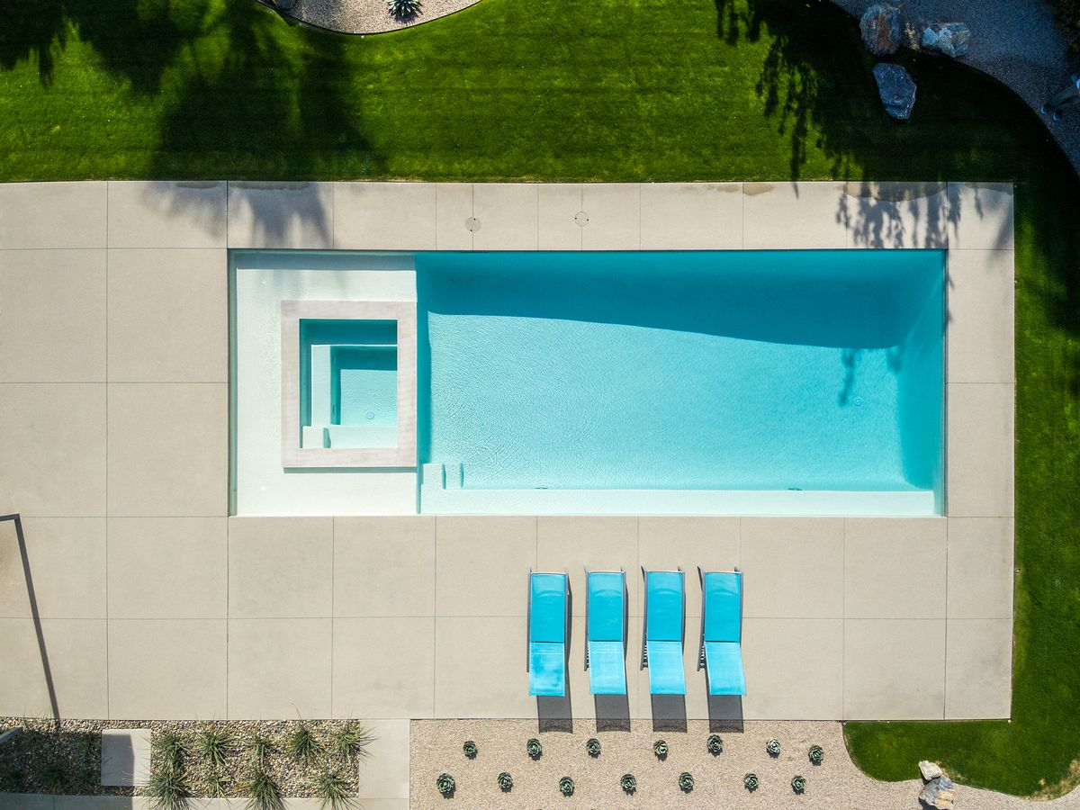 A view of the pool and spa from the sky. You can see the patio and four teal lawn chairs.