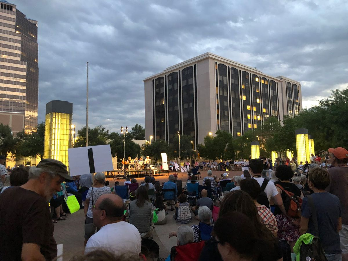 A large downtown plaza is filled with people listening to a presentation at the center.