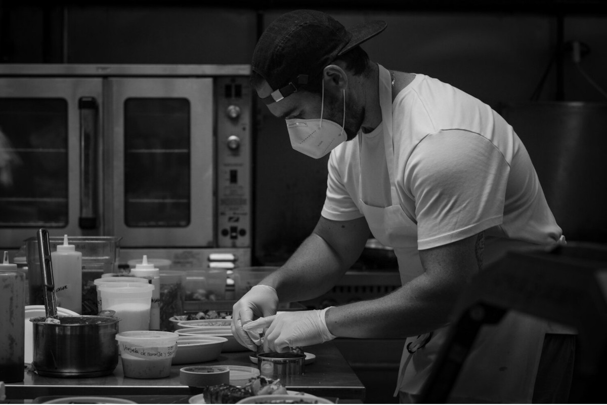 Black and white photo of chef Alejandro Tress as he prepares food in a kitchen, wearing a protective mask and a backwards cap