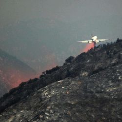 A DC-10 tanker drops fire retardant on a ridge line at the Angeles National Forest in California, Tuesday, Sept. 4, 2012. It could be a week before firefighters can contain this 3,600-acre blaze because of high temperatures and rugged terrain in thick brush that hasn't burned in a couple of decades.