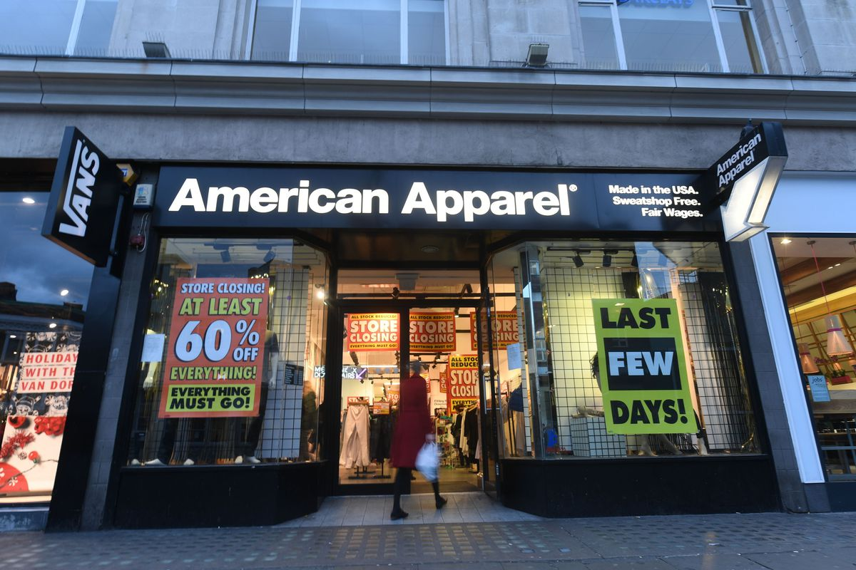 Signs in the window of an American Apparel store indicate massive markdowns.