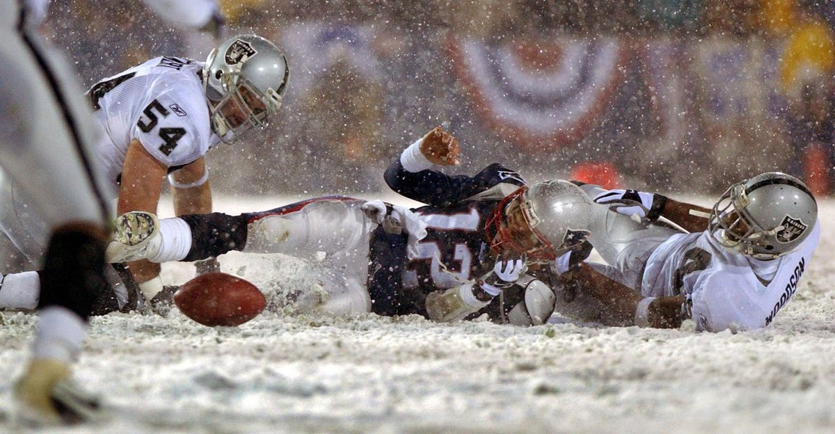 The fates of two NFL franchises hinge on the possession of this loose ball (Jim Davis/The Boston Globe via GettyImages)
