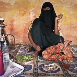 In this photo taken Tuesday, Sept. 18, 2012, prostitute Faduma Ali, who longs for the days when her pirate customers had money, chews the stimulant khat and smokes a cigarette at a house in the once-bustling pirate town of Galkayo, Somalia. The empty whisky bottles and overturned, sand-filled skiffs that litter this shoreline are signs that the heyday of Somali piracy may be over - most of the prostitutes are gone, the luxury cars repossessed, and pirates talk more about catching lobsters than seizing cargo ships.
