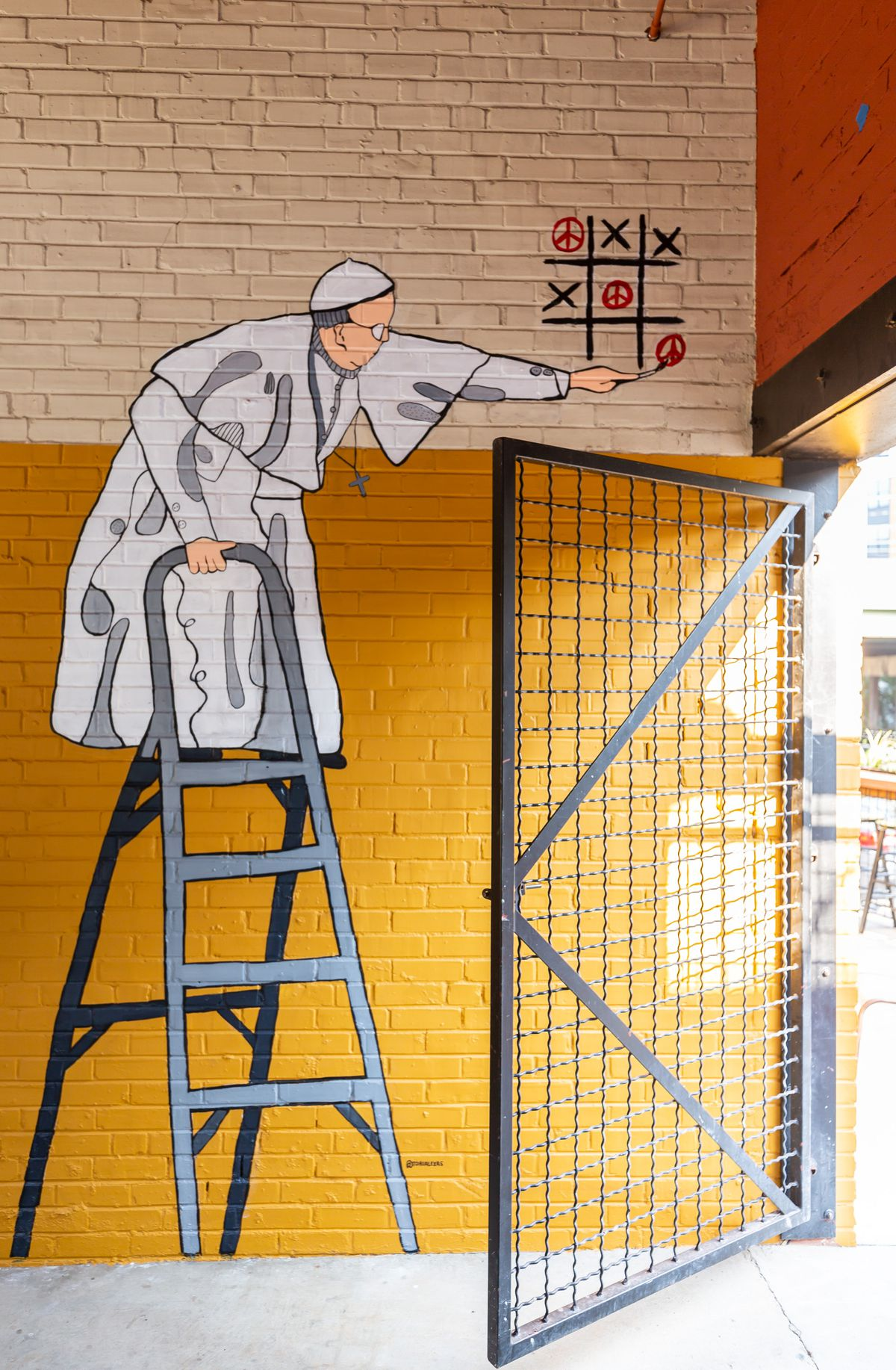 a painting on a brick wall of Rome's tic tac toe Pope on a ladder playing the game