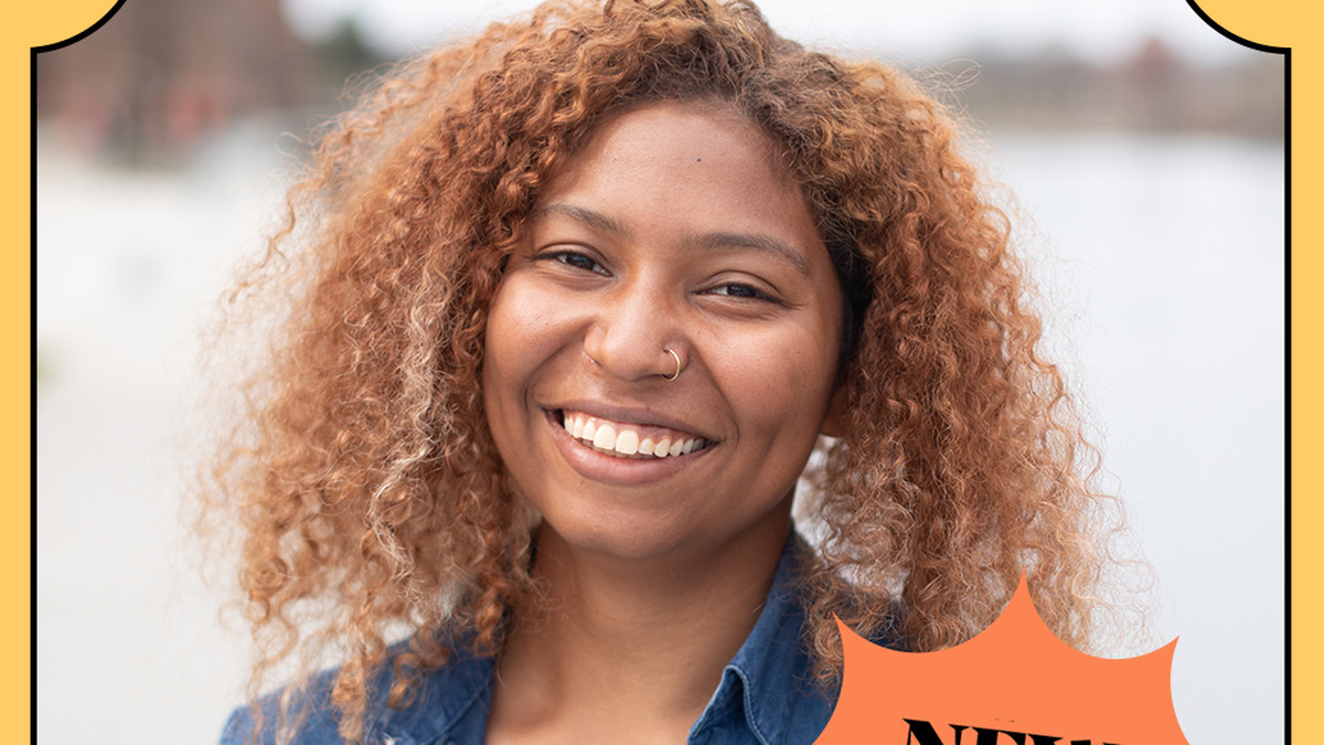 A Black person with curly light hair poses for the camera