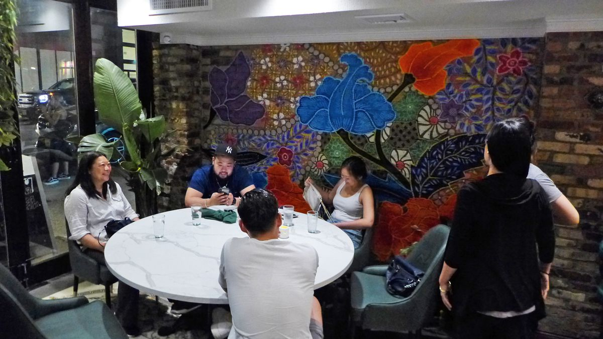 A round table of guests in front of a flower and foliage mural on the wall of the restaurant...