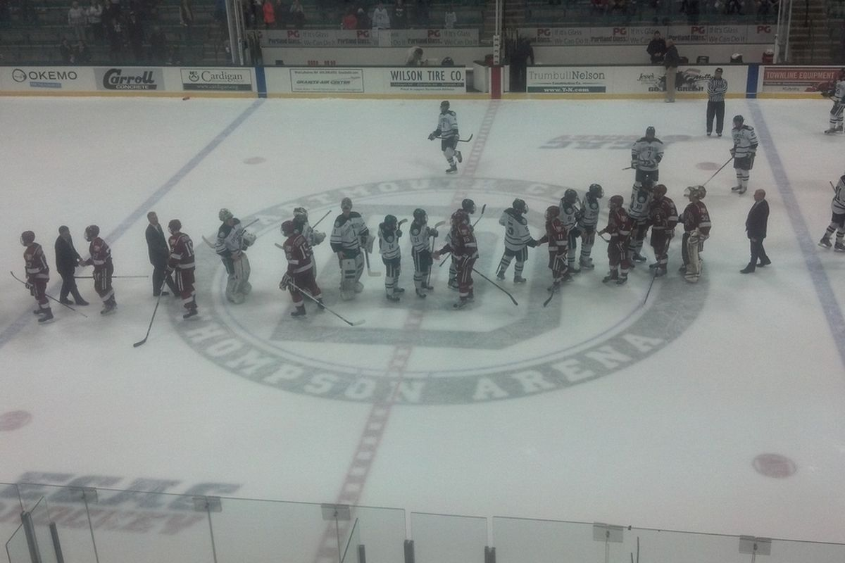 Harvard players shake hands with Dartmouth players following the Crimson's loss to the Big Green in the 2013 ECAC Tournament.