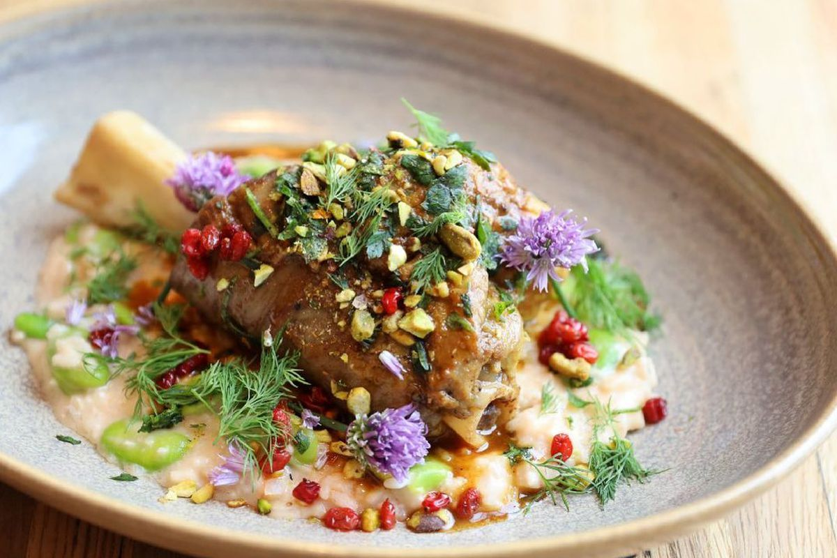 Braised lamb with saffron barberries and fava beans on top of creamy goat cheese rice from Roya