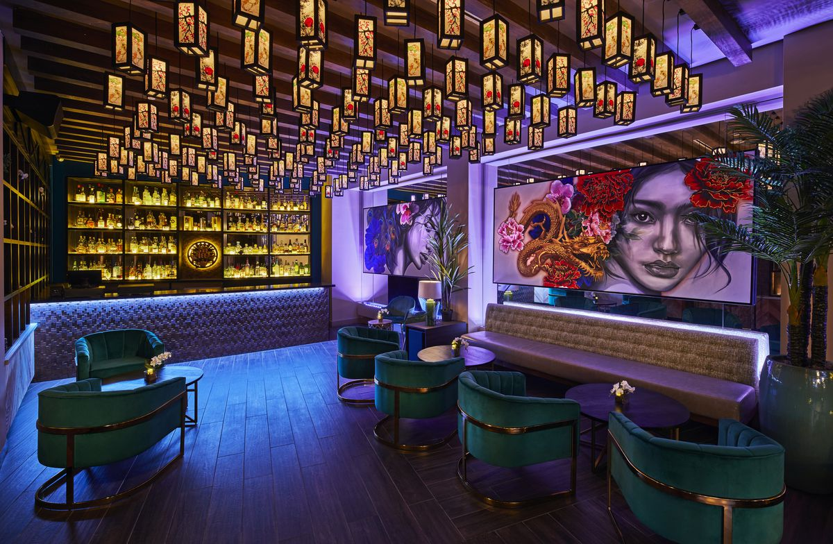 a dark list room with a bar in the back, colorful mural of a woman on the wall, seating, and lights hanging overhead