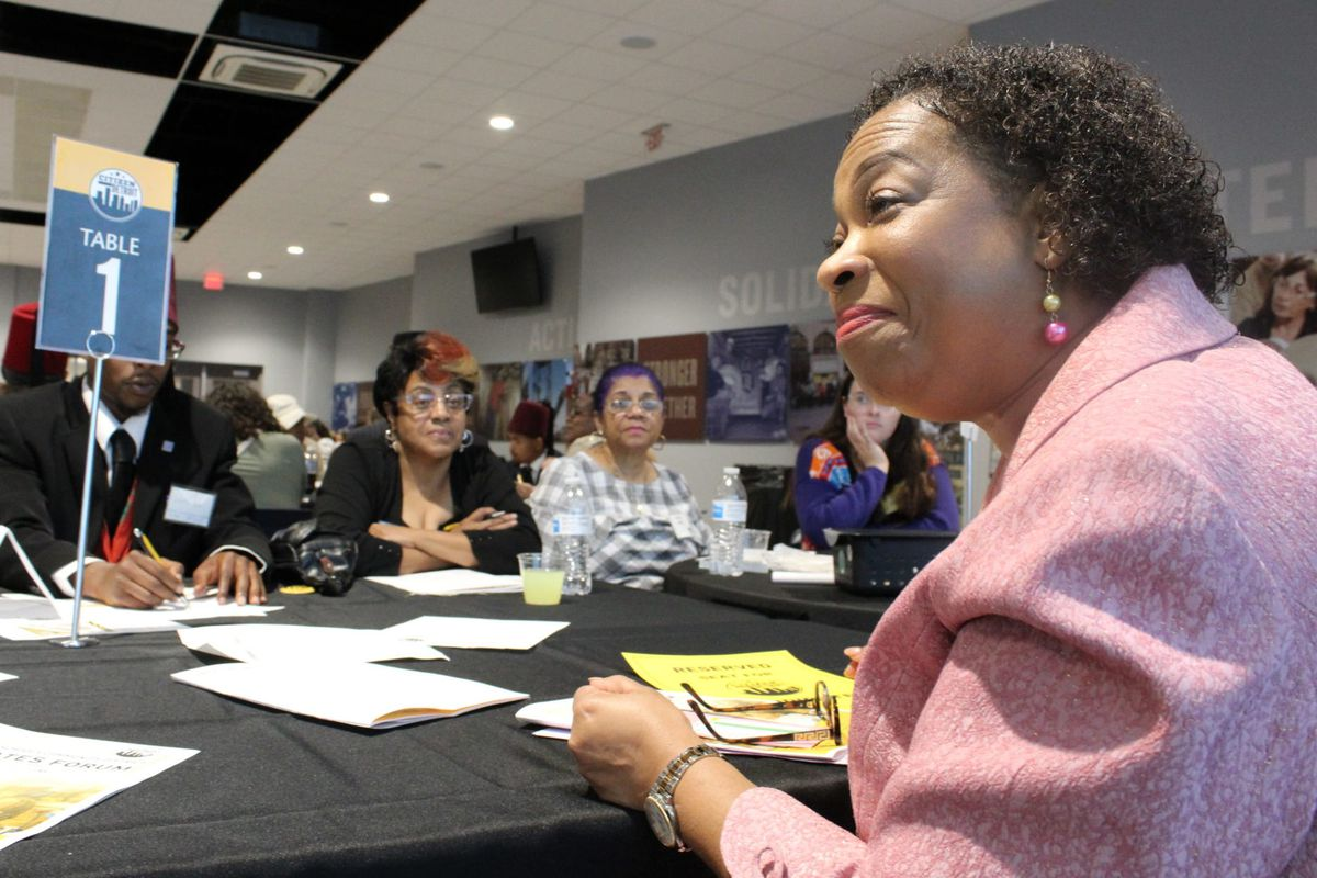 Corletta Vaughn, a candidate for Detroit school board, speaks to Detroiters at a forum Thursday evening as Nita Redmond (center) looks on. Vaughn says the district should be open to collaboration with charter schools and suburban districts.