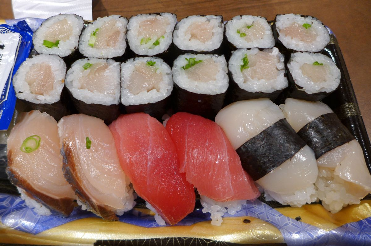Sushi in a plastic carryout tray includes three kinds of fish and a yellowtail and scallion maki roll.