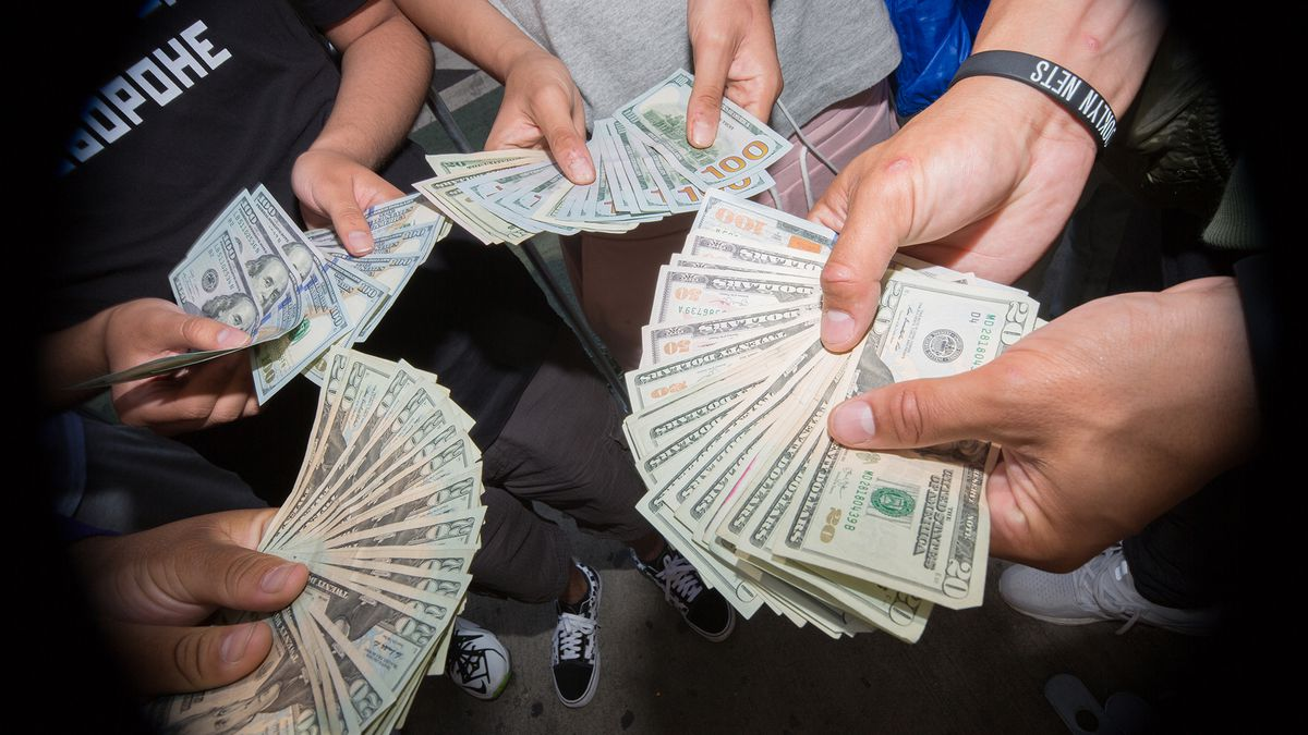 Four pairs of hands holding fanned-out cash