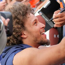 Broncos RB Phillip Lindsay smiles with fans while signing autographs.