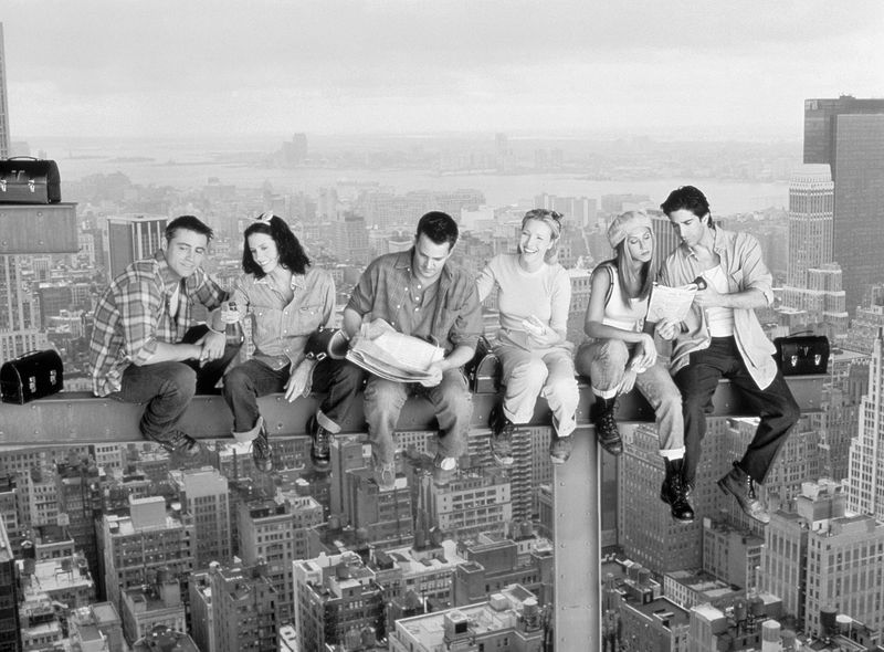 The cast of Friends in a promotional photo where they recreate a famous black and white photo of construction workers eating lunch while seated on agirderhigh above Manhattan.