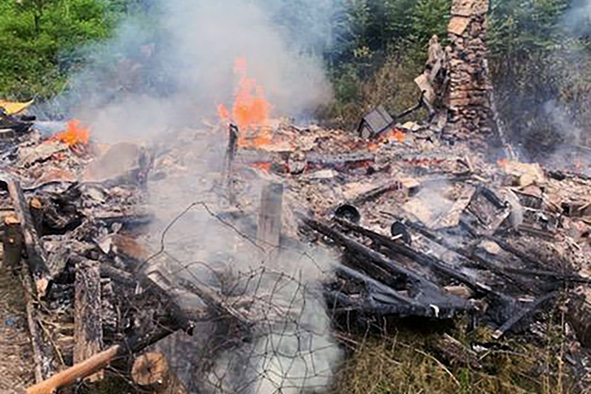 """Smoke rises Aug. 4 from the burnt remains of a cabin in Canterbury, N.H., inhabited by 81-year-old David """"River Dave"""" Lidstone, who for 27 years has lived in the woods of New Hampshire along the Merrimack River in the solar-paneled cabin."""