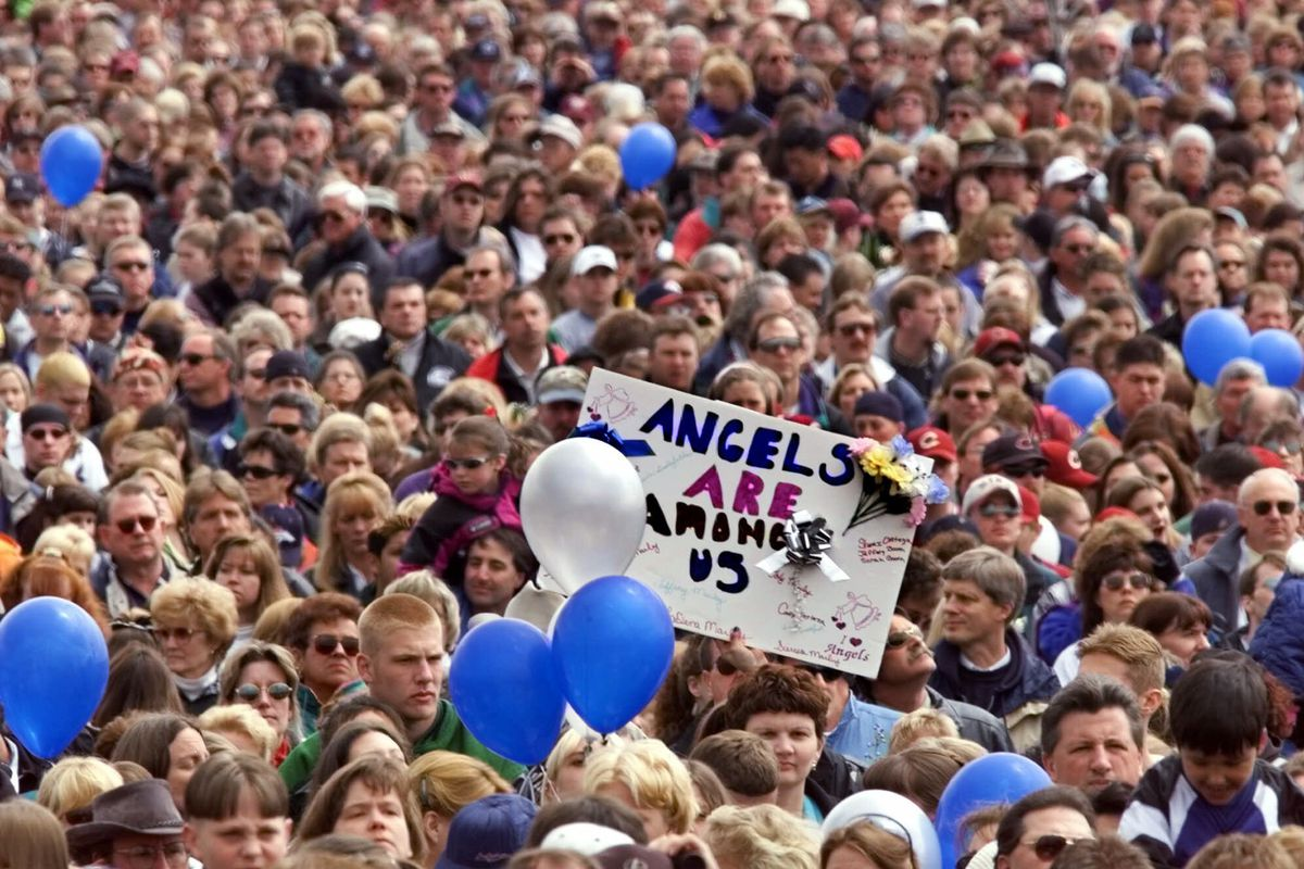 """A participant at a memoral service in Littleton, Colo., for the shooting victims at Columbine High School holds up a sign reading, """"Angles are Amoung Us,"""" during the service Sunday, April 25, 1999."""