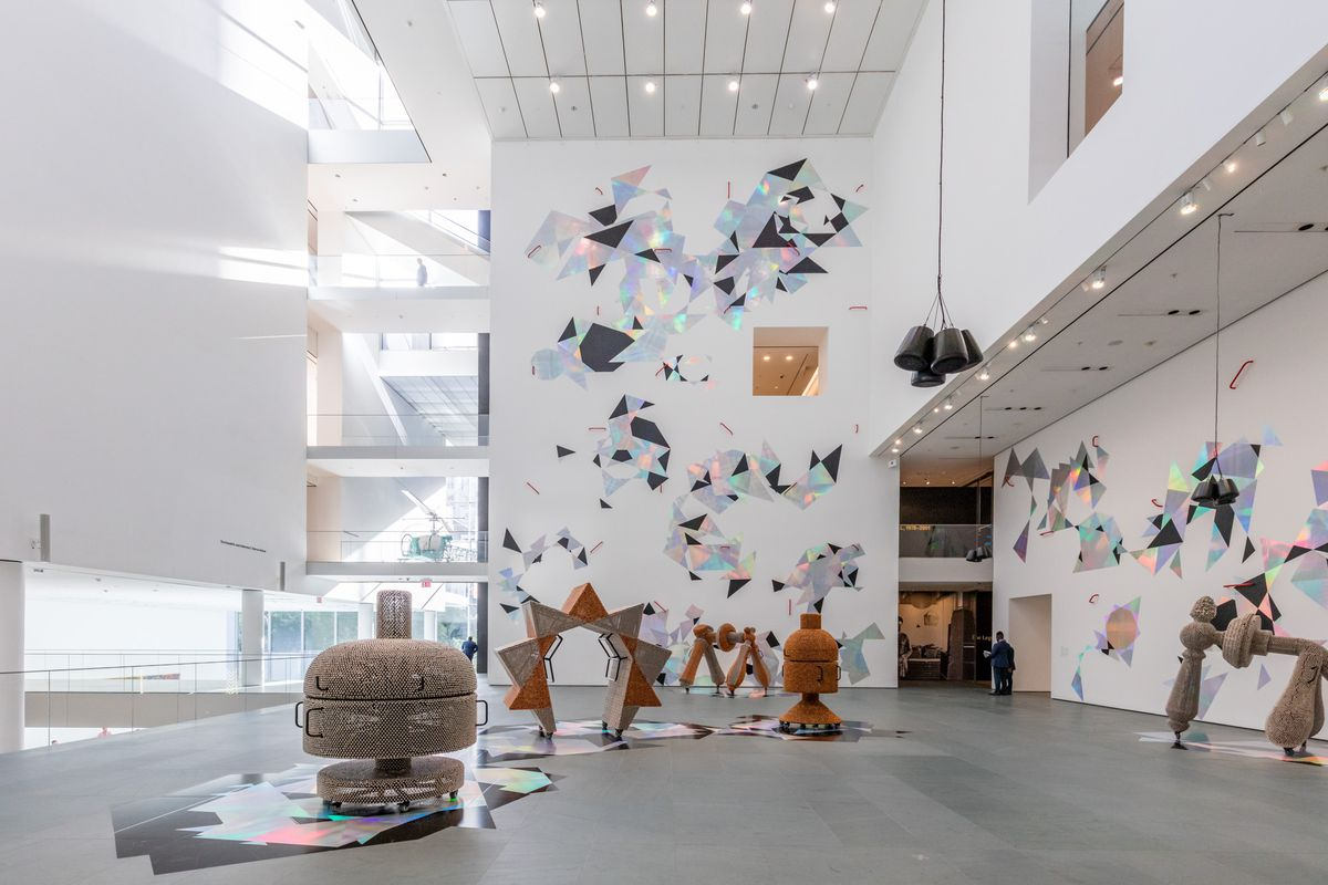 The atrium of a building with white walls. Sculptural works are on the gray floors, while iridescent patterns cover some walls.