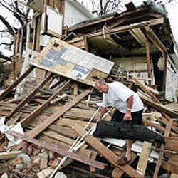 Ed Yarnell makes his way through the ruins of his house in Biloxi, Miss., Thursday.