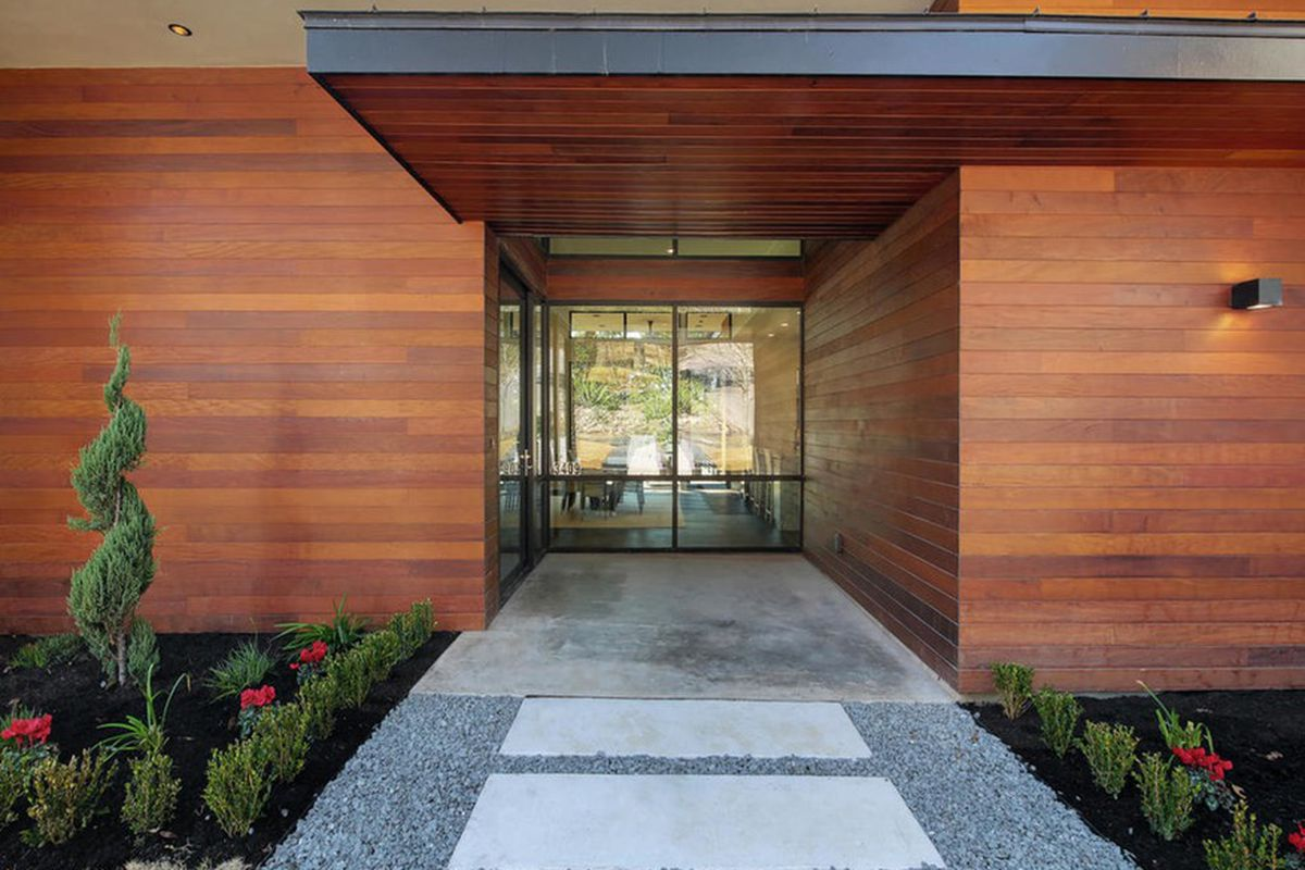 entrance to contemporary home with banded wooden walls on each side, view down middle to back windows, glass front door, flat overhanging porch roof, gray stone walkway