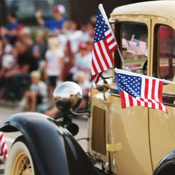 Flags wave during the Independence Day parade in Murray on Thursday, July 4, 2013.