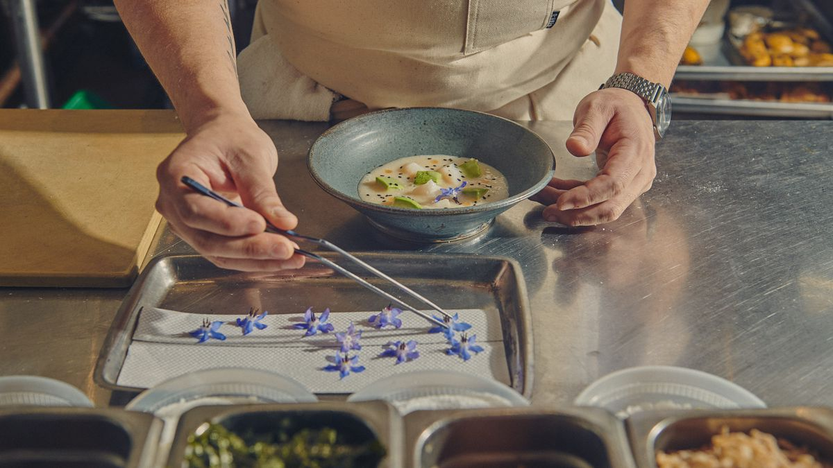 A chef uses tweezers to place purple borage flowers over a bowl of scallop ceviche with cherimoya