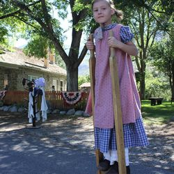 Stella Shurtz, 9, demonstrates how to use wooden stilts, a popular toy from the pioneer times in July 2014. Shurtz is one of over a dozen direct descendants of John Rowe Moyle who come to Moyle Park on Tuesdays to share the legacy of their pioneer ancestors with visitors.