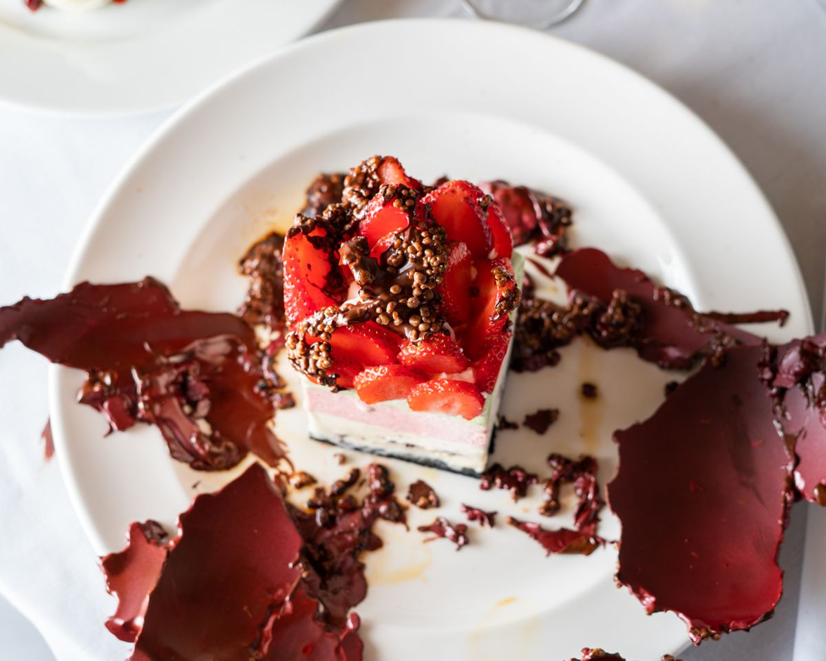 A strawberry dessert with chocolate on the side.
