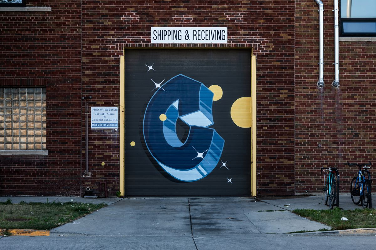 A brick warehouse's black garage door has a blue bubble letter spray painted on with white and yellow celestial accents. There is a glass block window and two parked bikes.