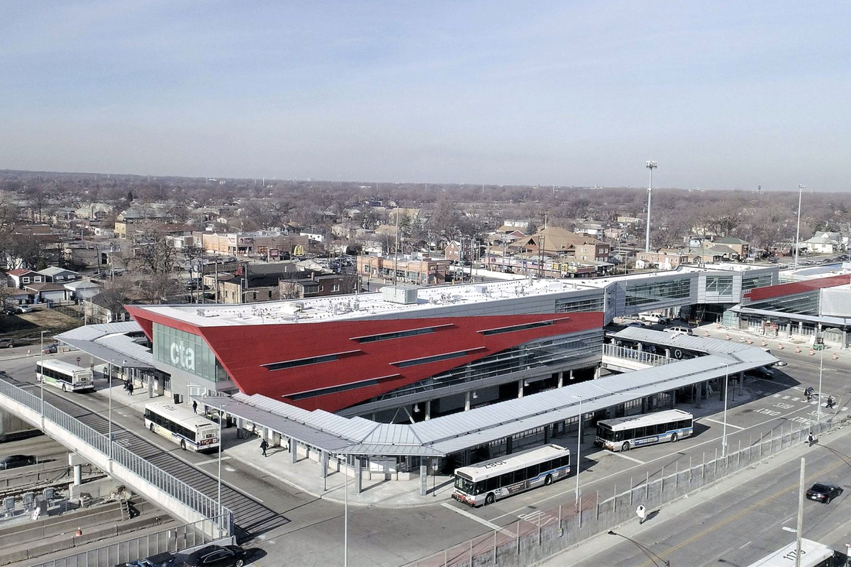 """An aerial view of a train and bus terminal with thin slit windows on a red and white sheet metal shelter with """"CTA"""" printed on the glass frontage."""