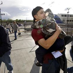 Cameron Brown, 7, greets his dad as he gets off a FrontRunner train in Clearfield. Russ Brown takes the train to work but says the 42-minute ride gives him way too much time to think about his family's challenges.