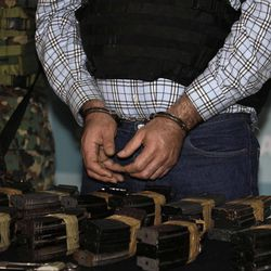 """The alleged leader of the Gulf drug cartel, Jorge Eduardo Costilla Sanchez, aka """"El Coss,"""" stands handcuffed before numerous assault rifle magazine clips during a media presentation at the Mexican Navy's Center for Advanced Naval Studies in Mexico City,Thursday, Sept. 13, 2012. One of Mexico's most-wanted men, the 41-year-old is charged in the U.S. with drug-trafficking and threatening U.S. law enforcement officials. U.S. authorities offered $5 million for information leading to his arrest."""